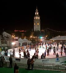 San Francisco Ferry building in background of lit up ice rink with guests skating